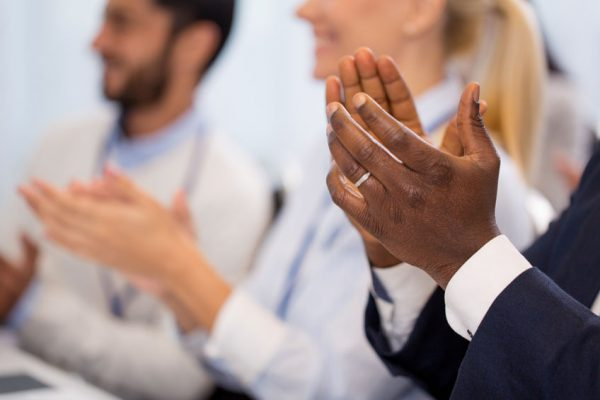 business and education concept - group of people applauding at international conference